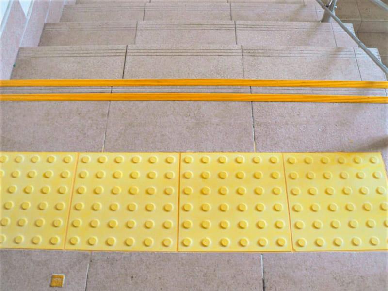 Тактильная плитка из полимербетона у лестницы